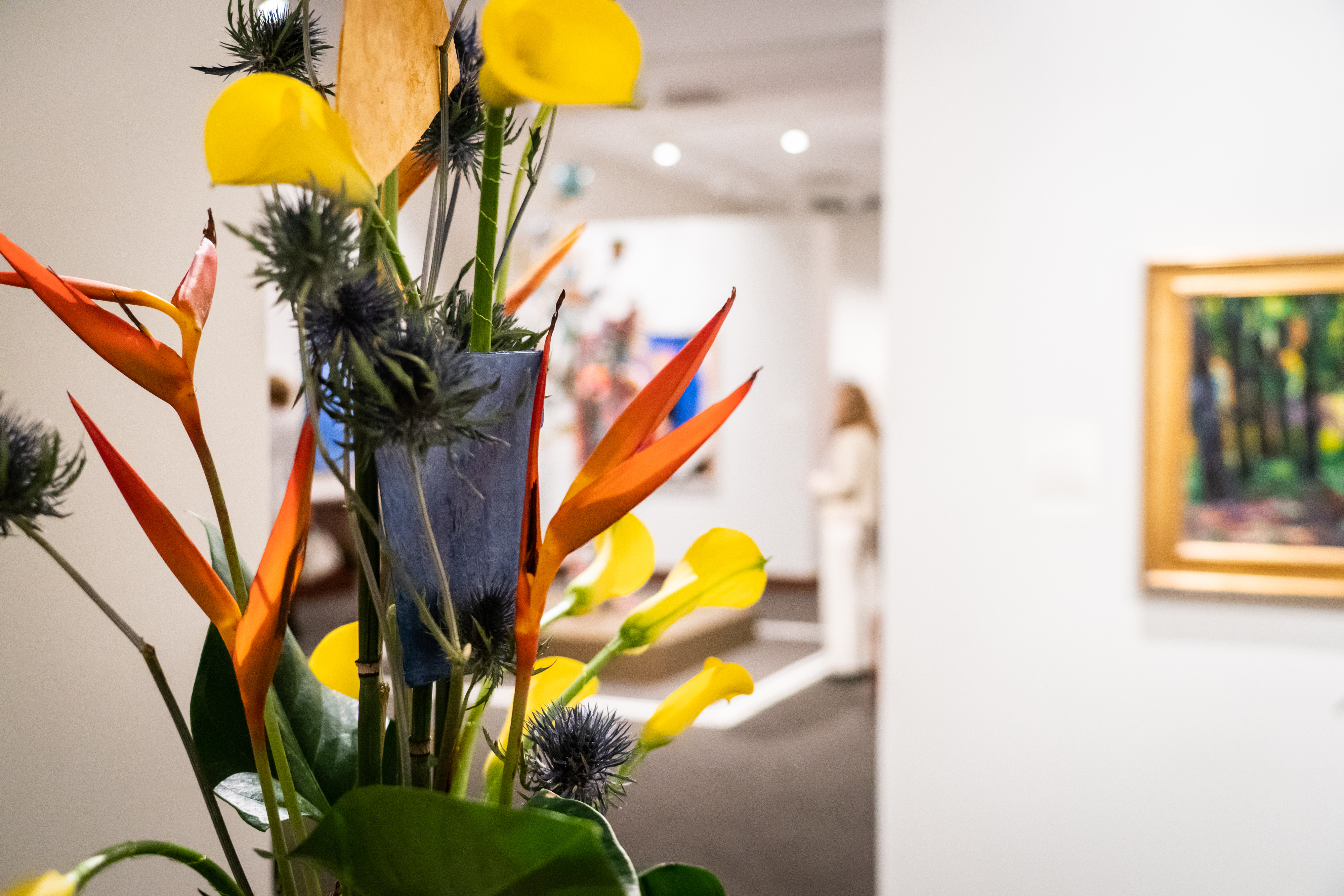 The camera is focused on a colorful floral arrangement in the MAM galleries. Further back and out of focus, a painting is hanging on the wall and a woman is looking at Nick Cave's sound suit.