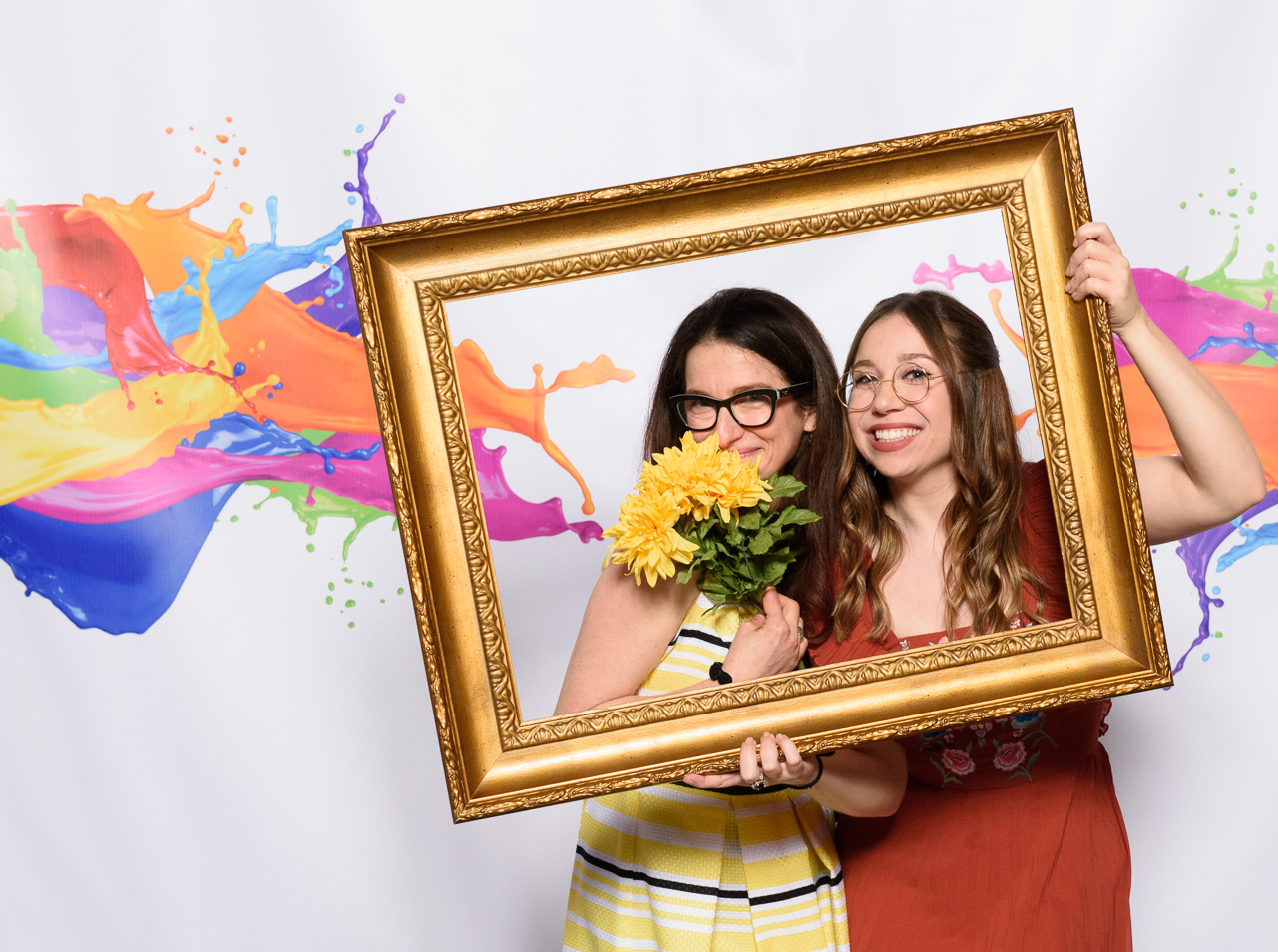 Two young women are posing in front of a colorful backdrop with an empty picture frame and fake flowers