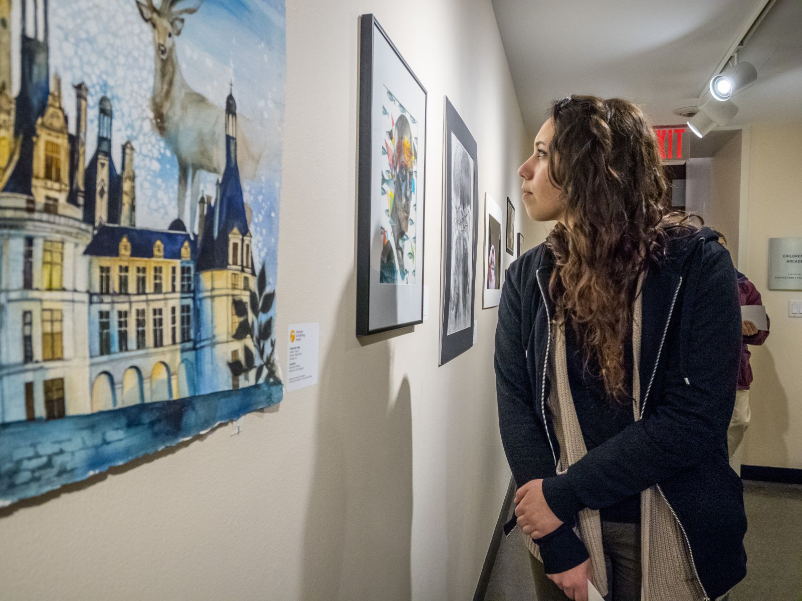 A teen is looking at the scholstic art award winners' artworks hanging on a wall in MAM.