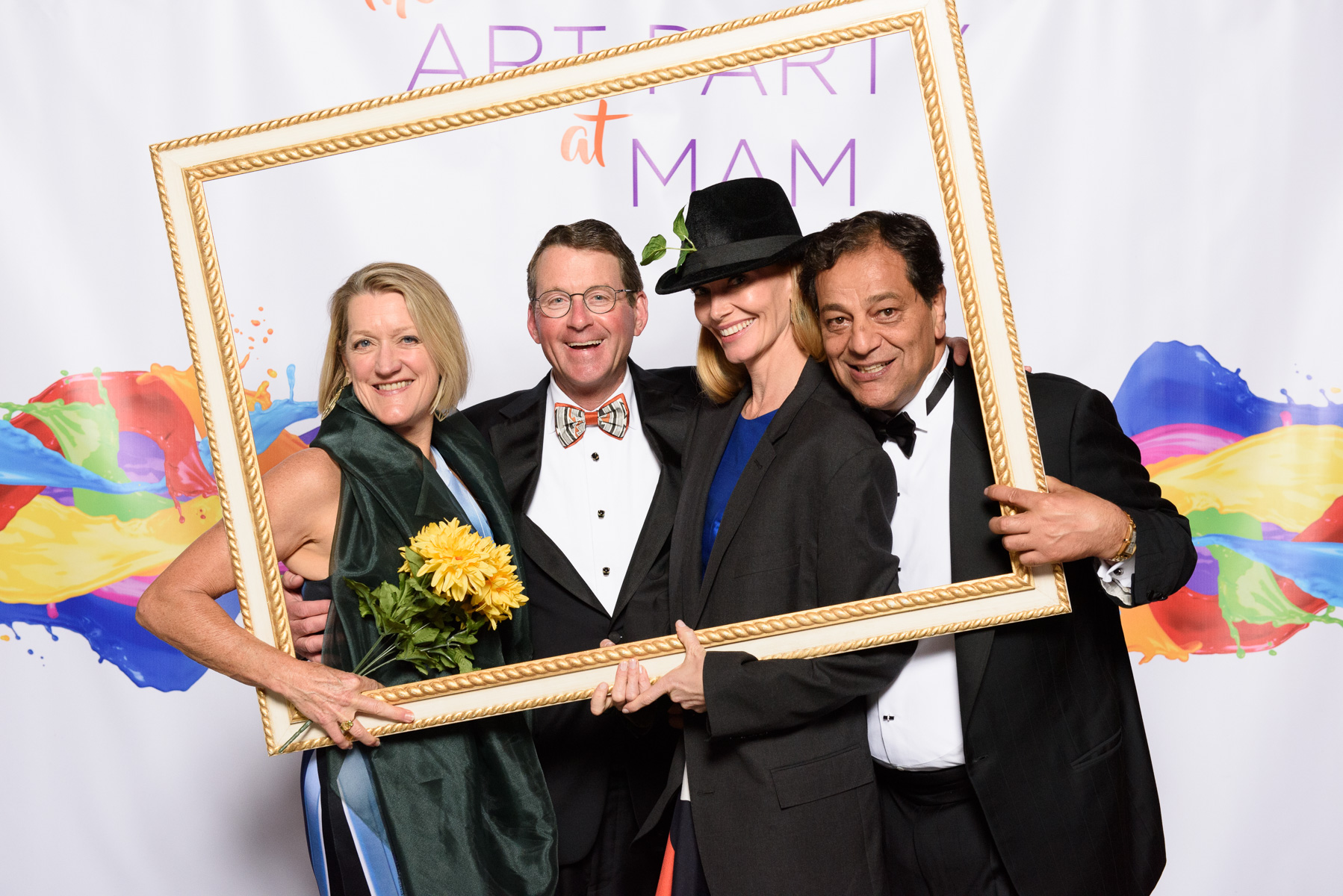 Four Patrons attending the Art Party pose in front of a banner with an empty picture frame