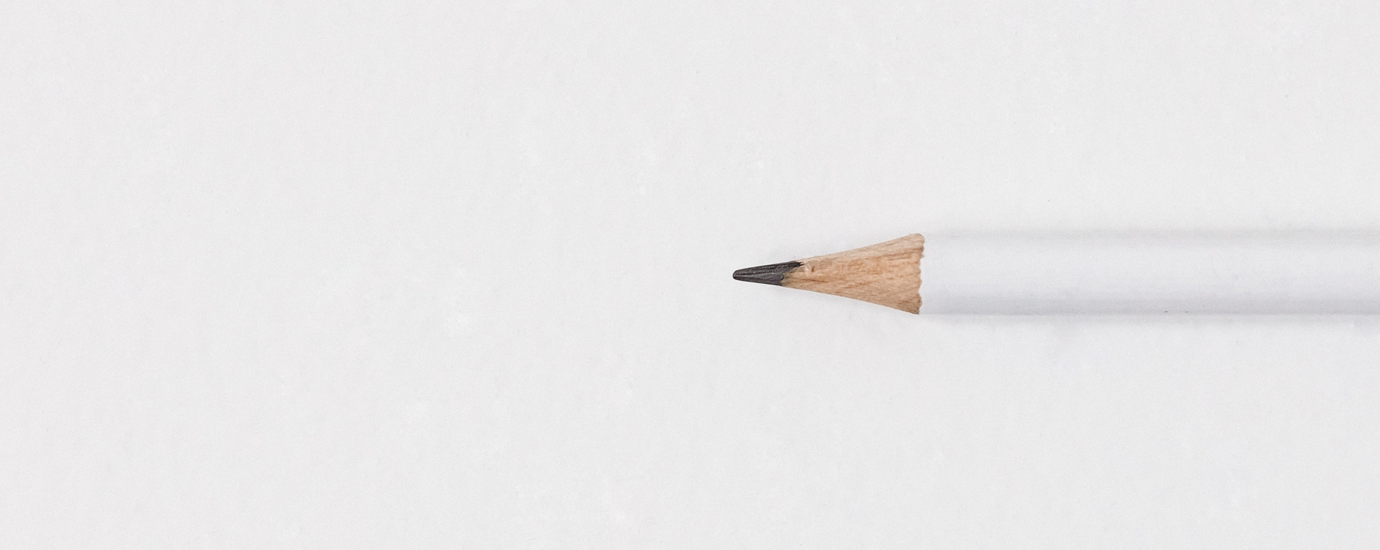 a pencil sitting on a white surface