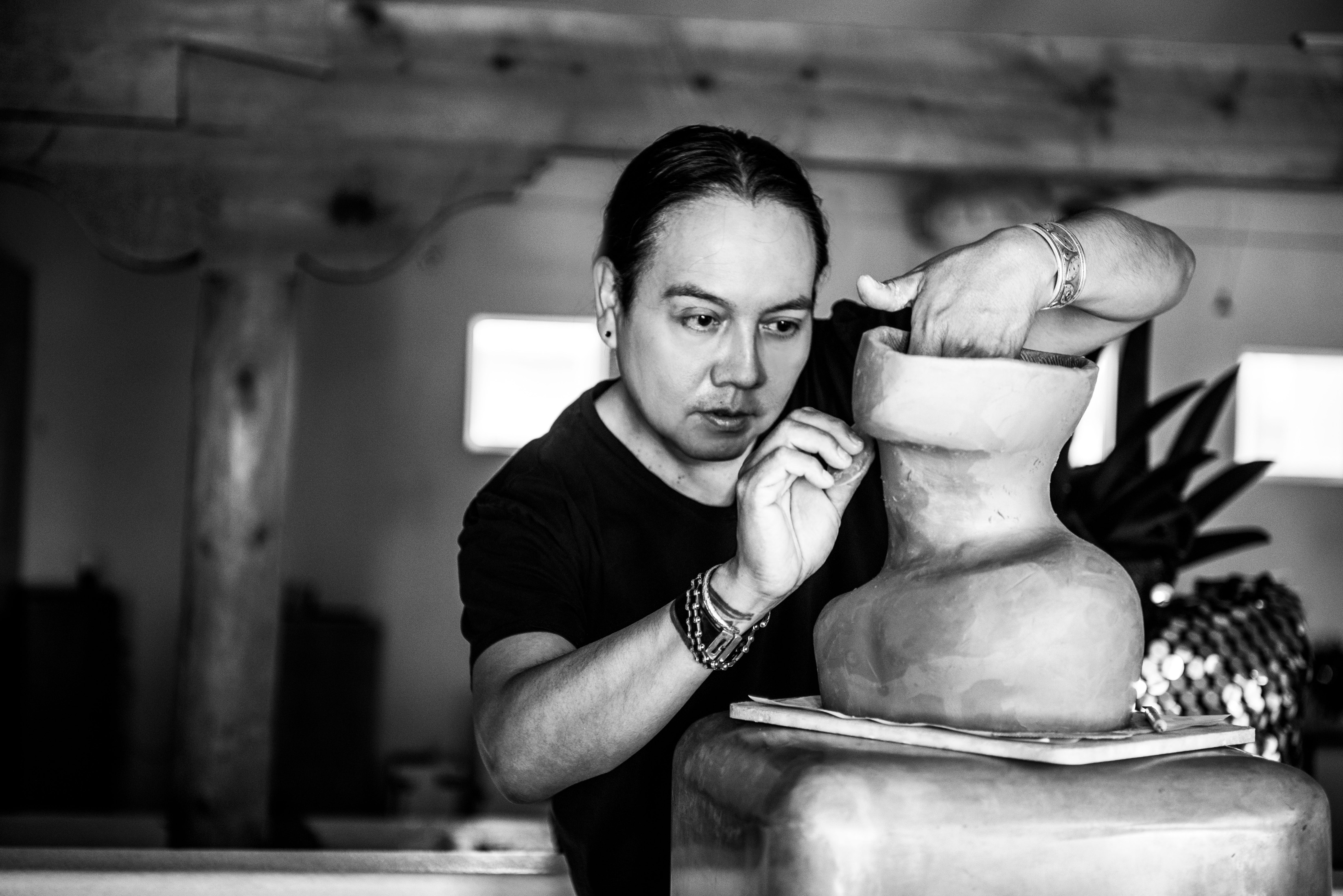 I'm an image! Virgil Ortiz sculpting clay by hand in his studio. Ortiz is focused on his work and not looking at the camera.
