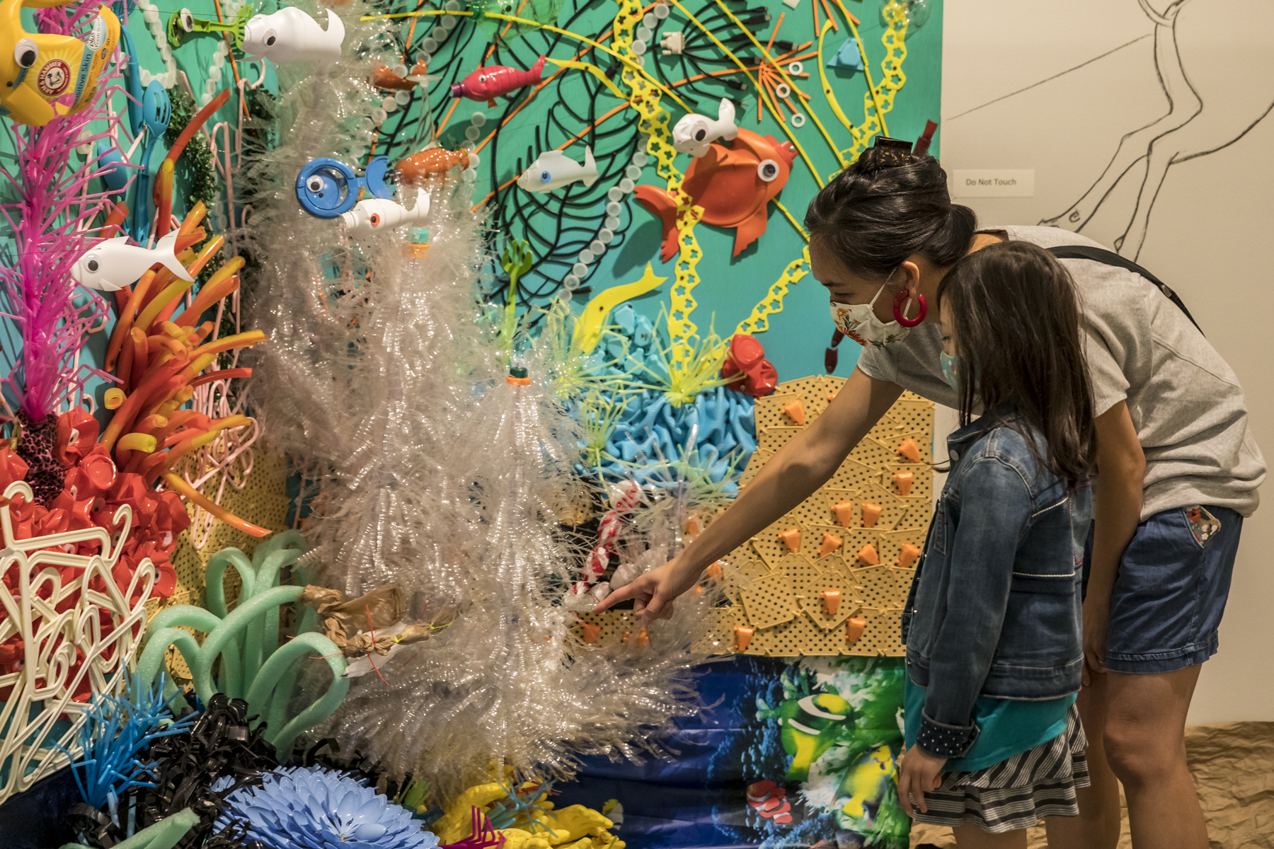 A child and her mother are looking at Federico Uribe's coral reef installation. The mother is pointing to something. The child is looking at where she is pointing.