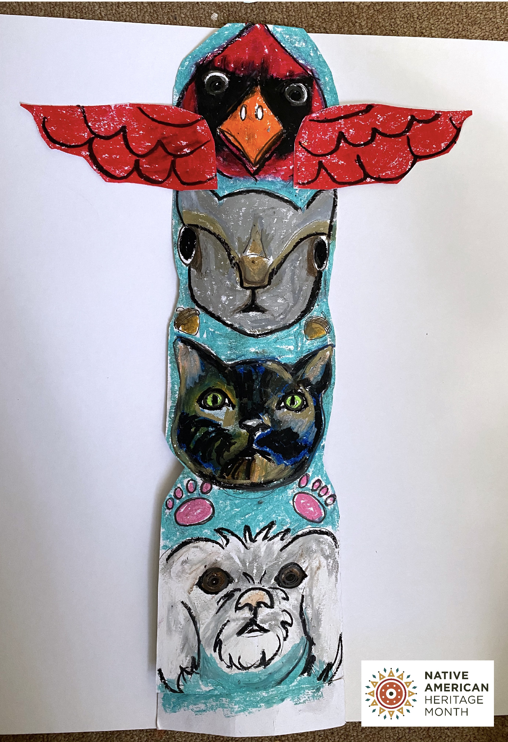 Totem pole project featuring a cardinal, rabbit, cat and dog from top to bottom. Bottom right corner has NAtive American HEritage month logo.