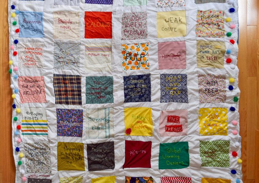 This is a 6 foot by 6 foot handmade quilt that features different colored squares with hand stitched grievances.