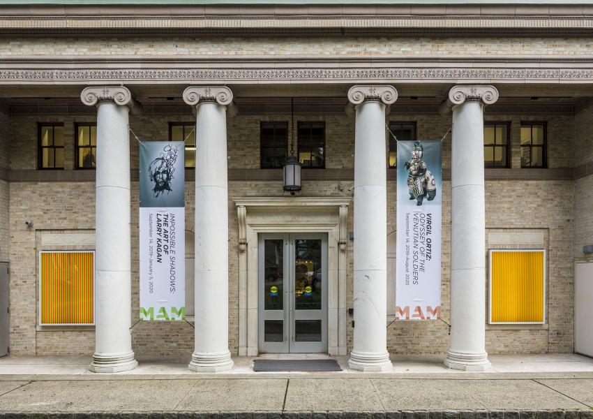 exterior photo of the Museum featuring banners of Virgil Ortiz and Larry Kagan
