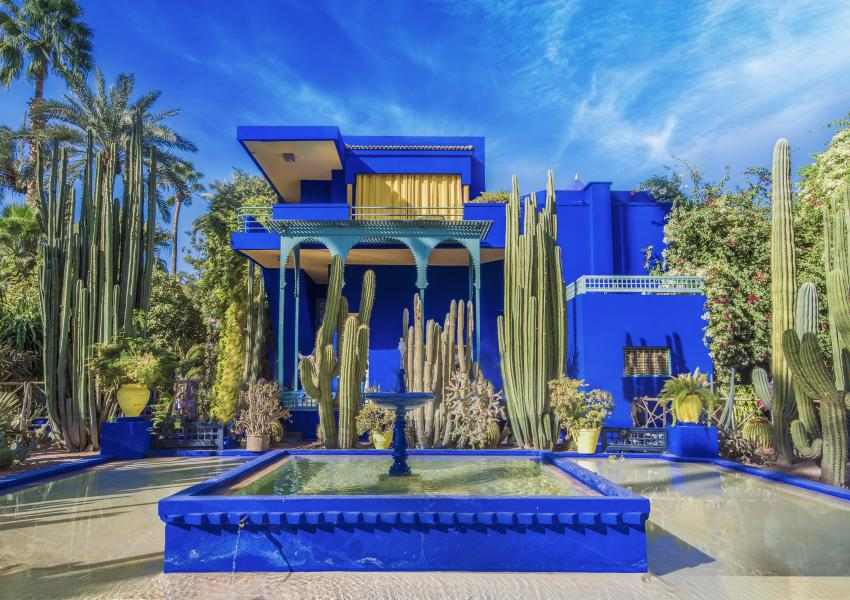 This image is of the Majorelle Garden and Yves Saint Laurant home in Marrakech, Morocco.  The home is a vibrant blue and features a large, square fountain in front of it.
