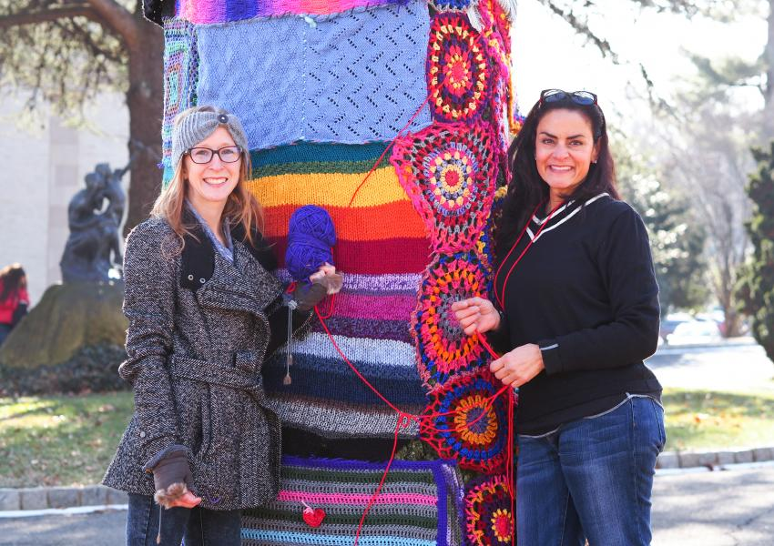 Two volunteers posing next to a large, wide tree trunk that they just decorated with knitted pieces during the MAM Yarn Bomb.