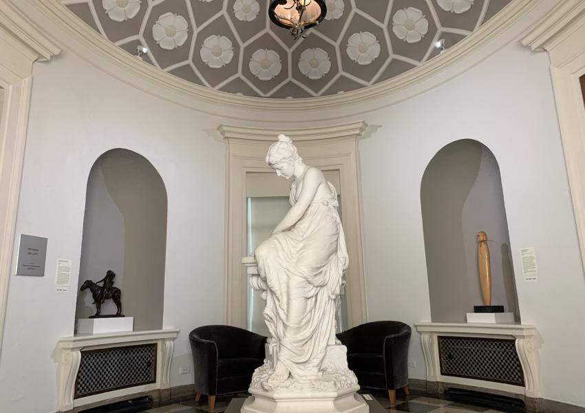 The rotunda gallery at MM, a small round gallery. In the center is a marble sculture showing a woman creating a crown out of olive branches.