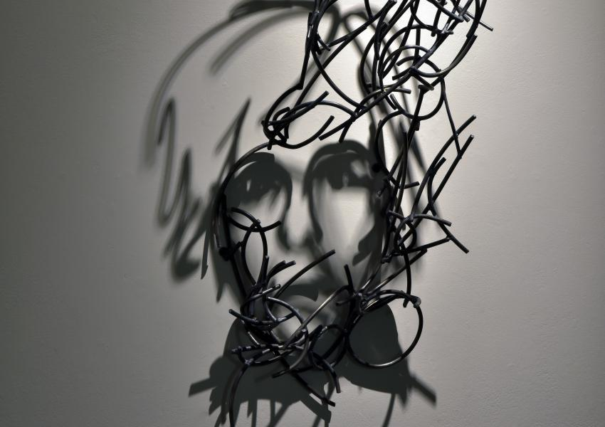 Larry Kagan's metal sculpture hanging on the wall, casting a shadow that looks like a portrait of andy warhol.