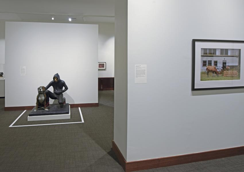 Gallery view in the uncaged exhibition. A painting and a sculpture of a teen and dog are in view.
