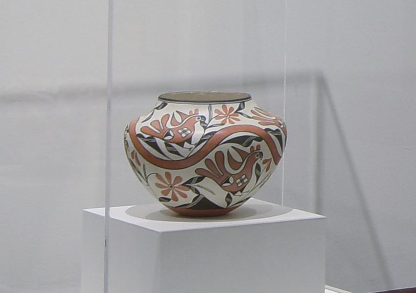a traditional hanndmade ceramic pot in a glass case in a MAM gallery.