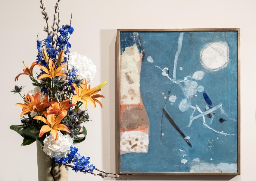 a tall skinny floral arrangement with lillies and other flowers is in front and to the left of an abstract artwork
