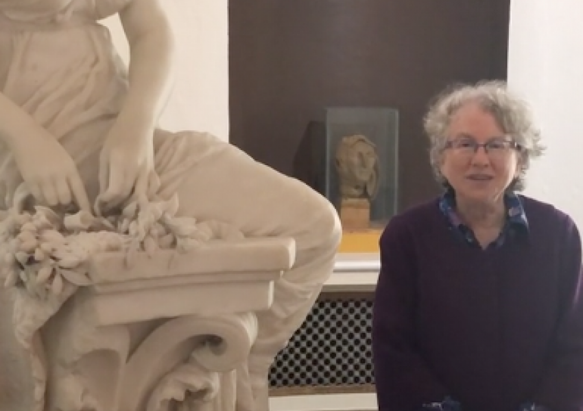 chief Curator Gail Stavistky is standing in the rotunda gallery, dwarfed by the crown for the victor sculpture on her left, and in front of a wax head sculpture.