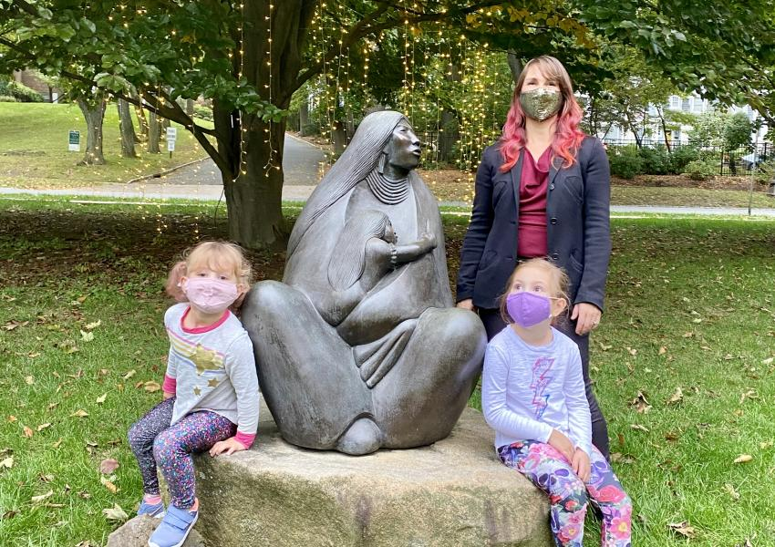 A family is posing around the outdoor earth mother sculpture at MAM.