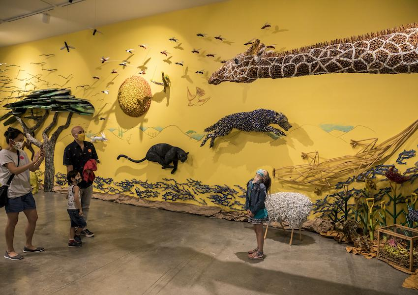 A family is exploring the Federico uribe: animalia exhibition together.