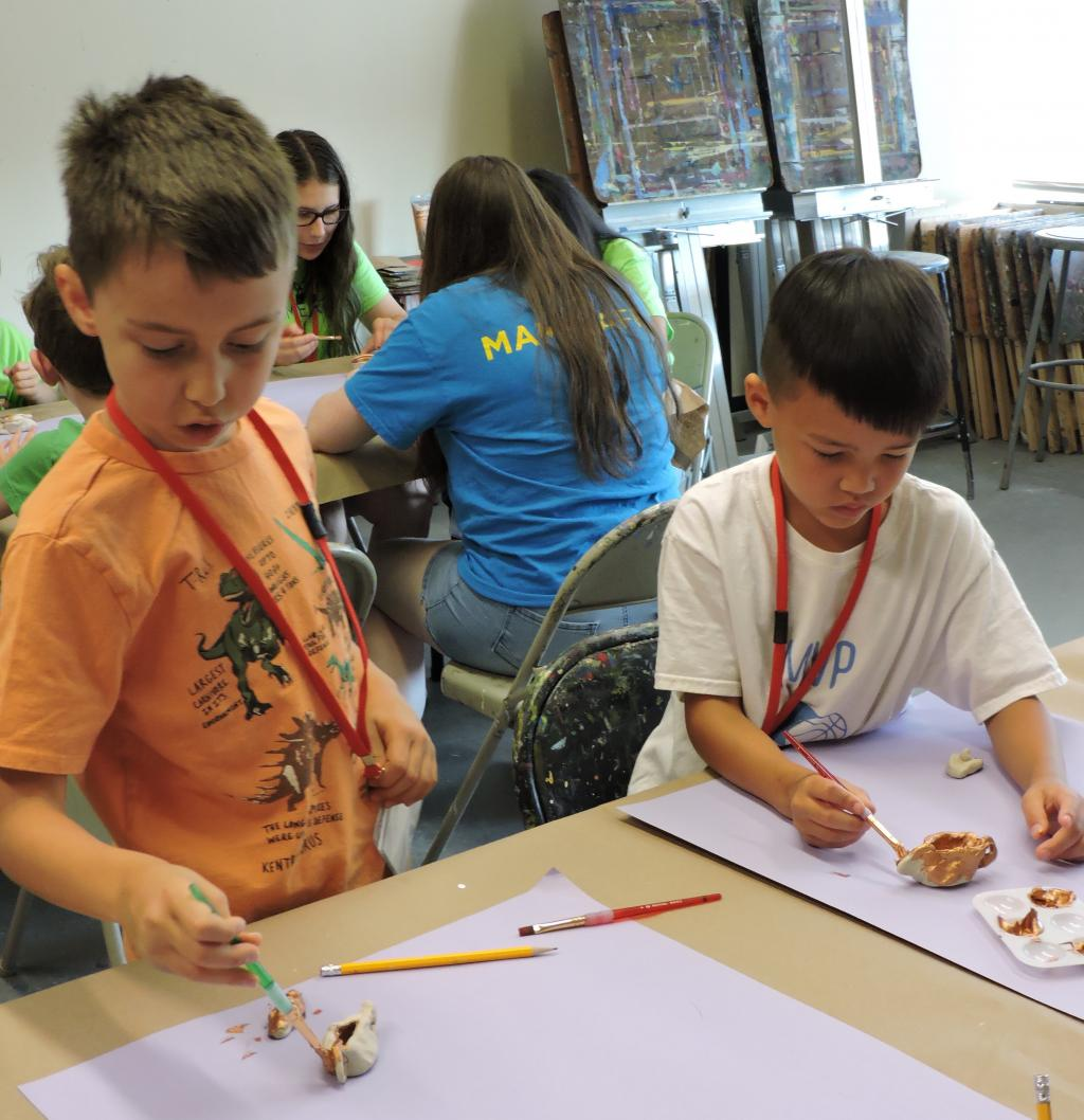 Two children are painting their small clay creations. They are both focused and not looking at the camera.