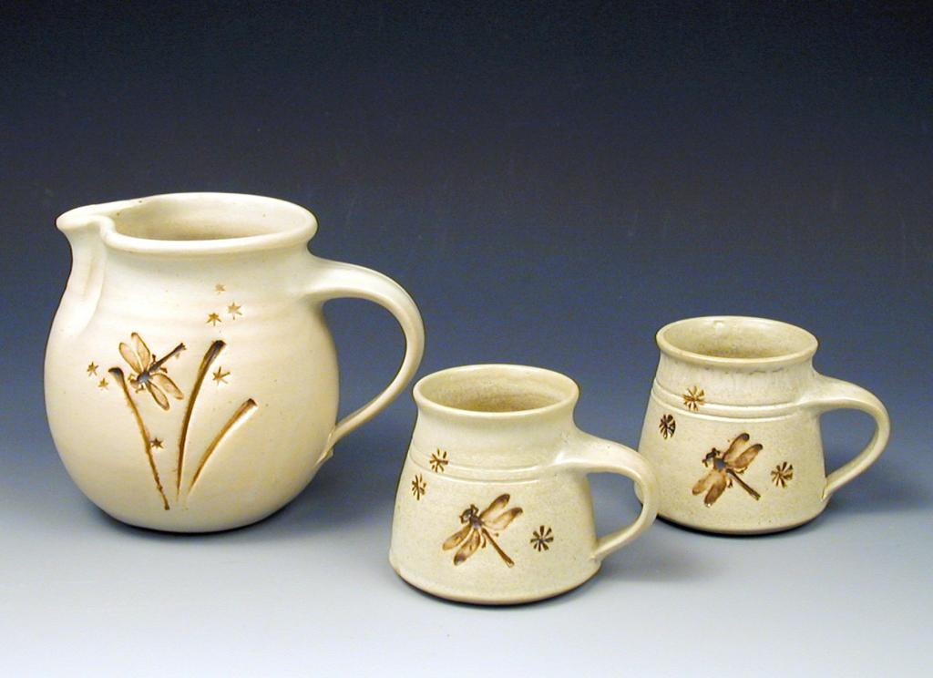 A creme colored pitcher and two mugs, created by hand on the pottery wheel. They've been set up on a backdrop for professional photography.