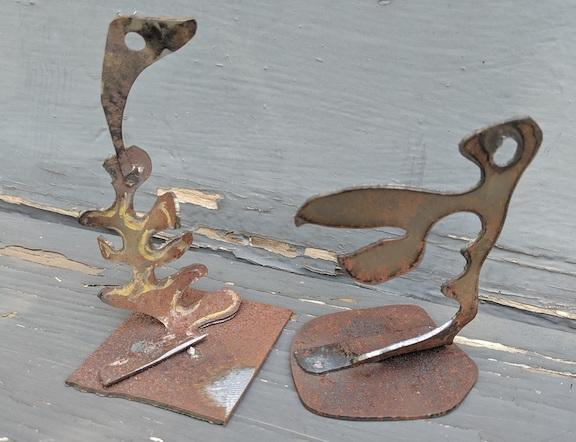 Two small abstract metal sculptures are sitting on a table.