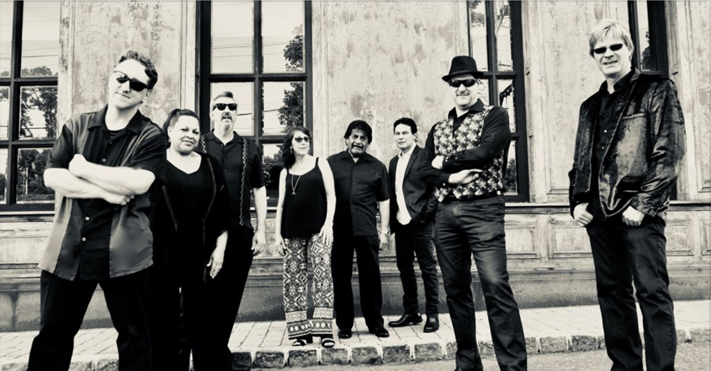 Eight members of the Steely Dan Cover band, The Royal Scam are standing on a street and sidewalk. Black and white image.