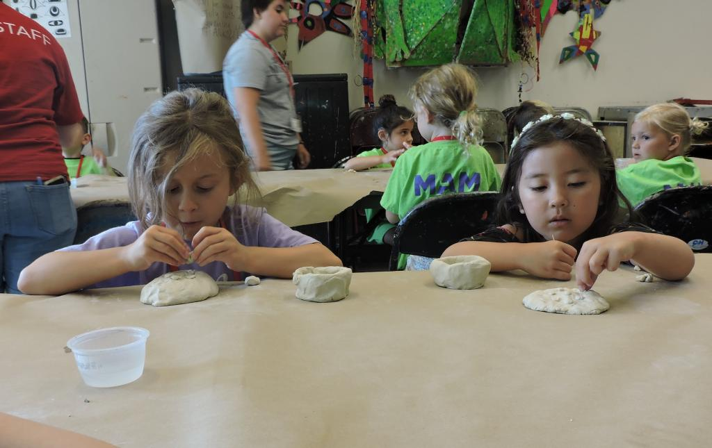 two children are working at a table next to each other on clay projects. They are both focused on their artwork and not looking at the camera.