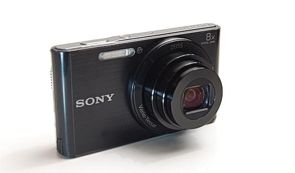 A small, black Sony point-and-shoot camera on a white background.