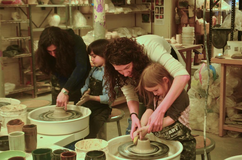 Two pairs of mothers and children are at pottery wheels in the ceramic studio. Both pairs are leaning over the wheels, focused on their clay.
