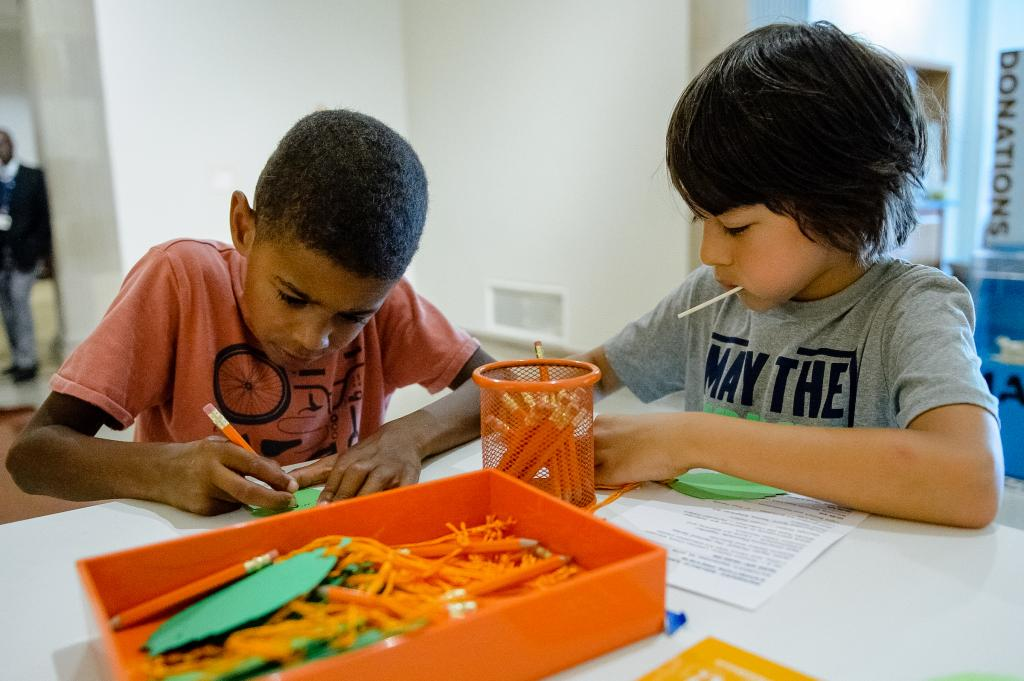 Two children are working on projects at a table together in Drop-in studio.