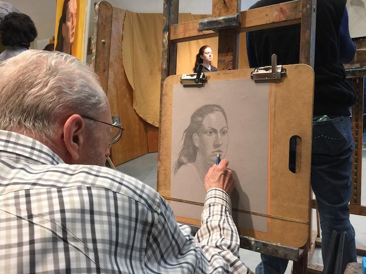 A student is sitting at an easel, drawing a portrait of a woman with a pencil.