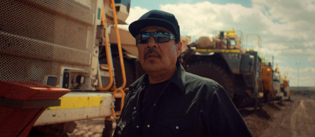 A still from the film The Blessing. A man is standing in front of large construction vehicles and machinery. He is wearing sunglasses and a baseball hat.