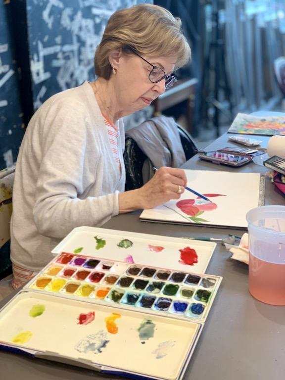A Woman is painting with water colors. She has a palette next to her with over 30 paint colors.