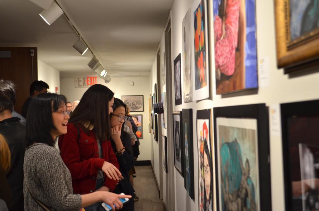 Visitors look at a hallway full of students gold-key-winning artworks.