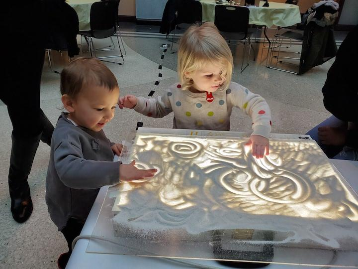 Two children are playing with sand that is on top of a lightbox. They are making shapes with the sand with their fingers.