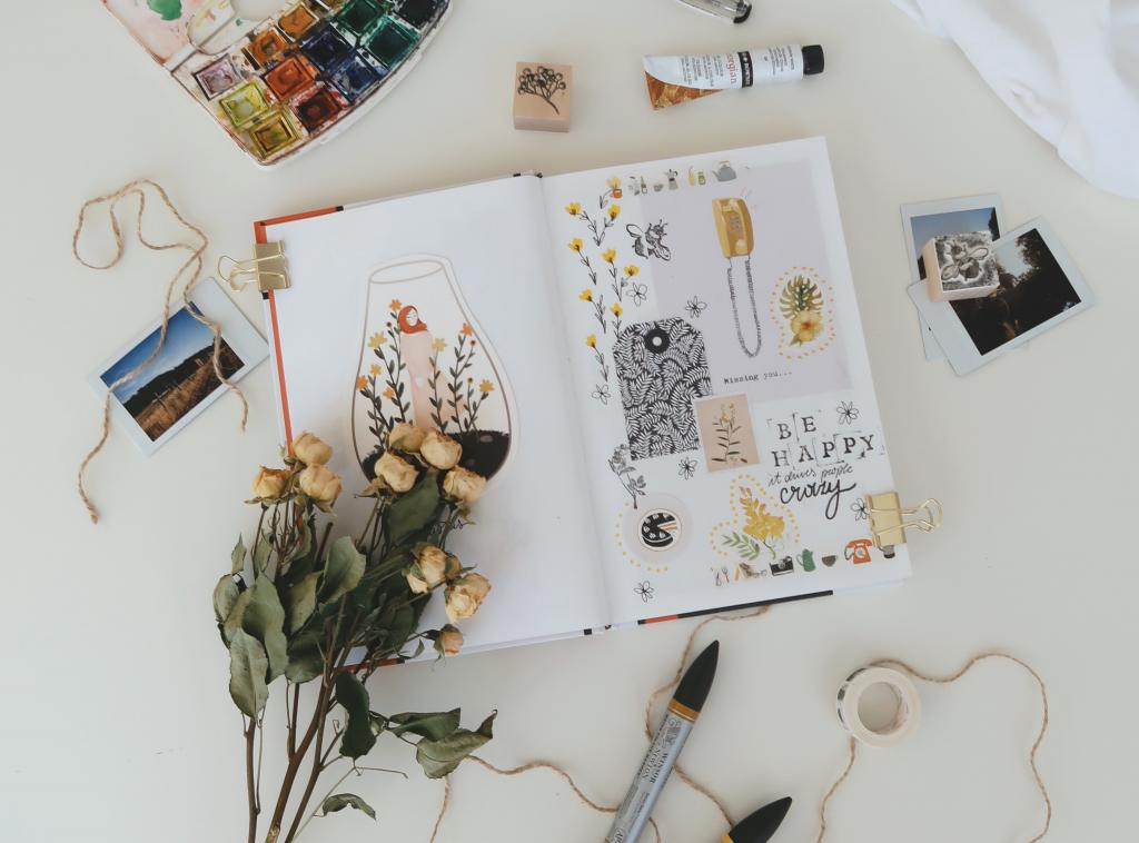 a journal is laid flat on a desk with art supplies and fried flowers surrounding it. There is a collage of found items and drawings on the open pages.