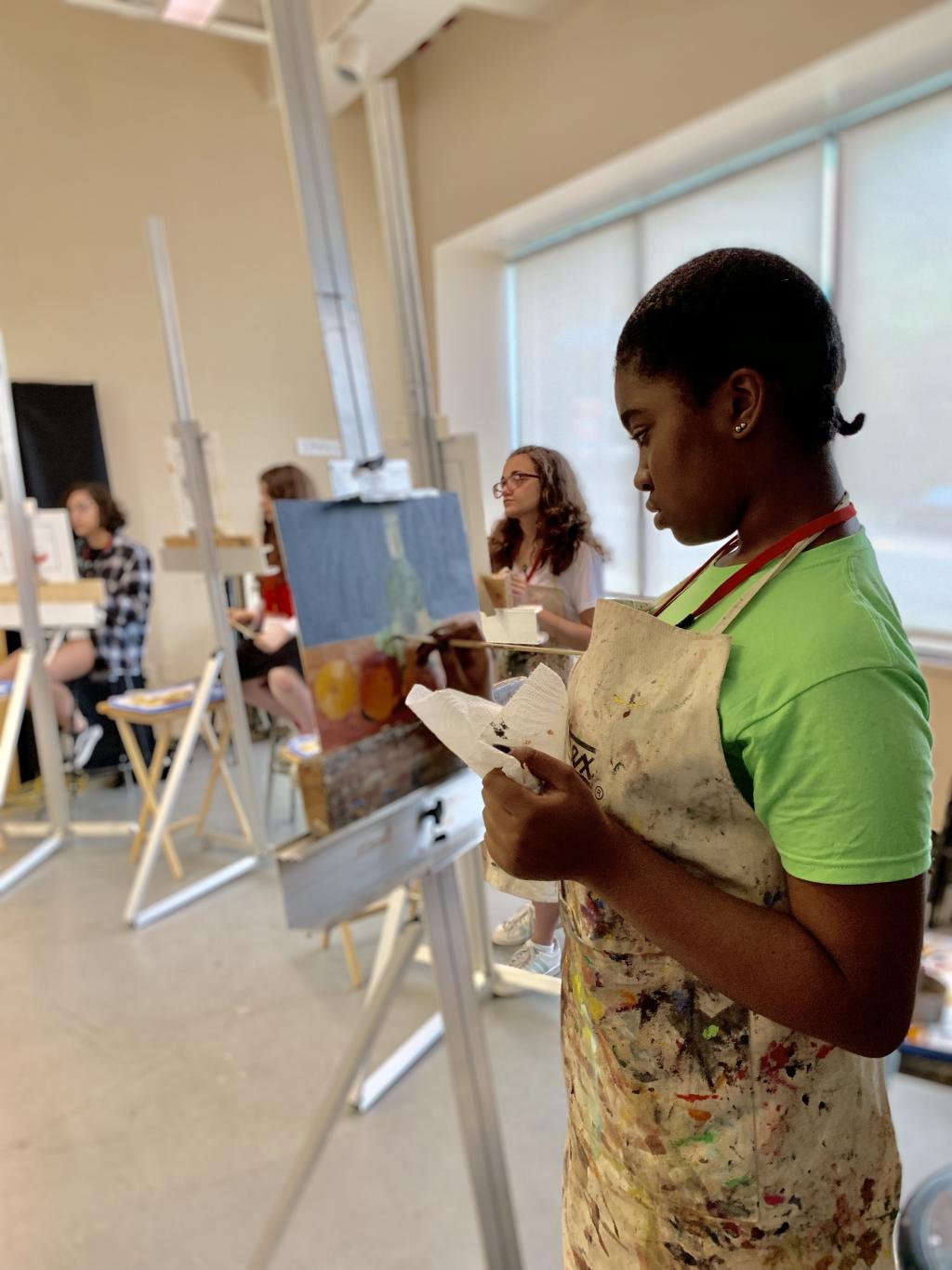 a teen student is painting on an easel. She is not facing the camera.