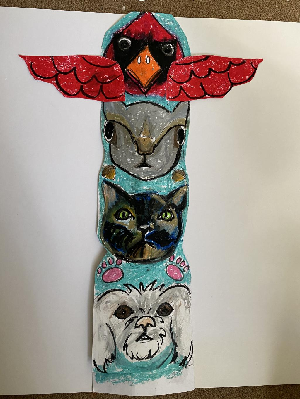 A totem pole drawn on paper featuring a cardinal, a rabbit, a cat and a dog from top to bottom.