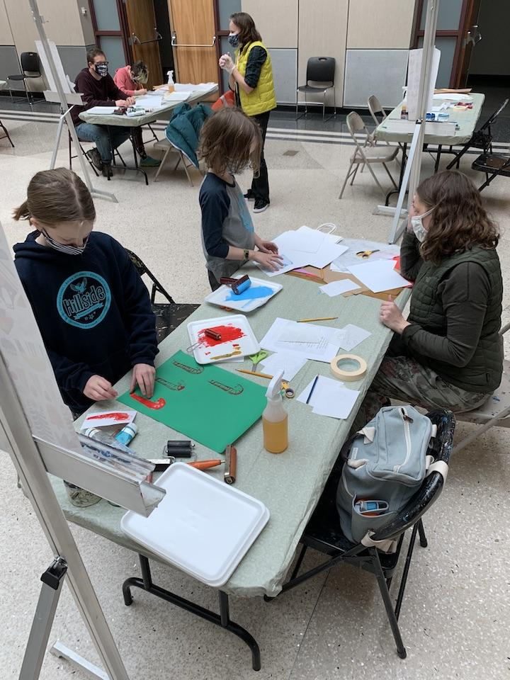 Families working on printmaking artworks at spaced out tables in Leir Hall.
