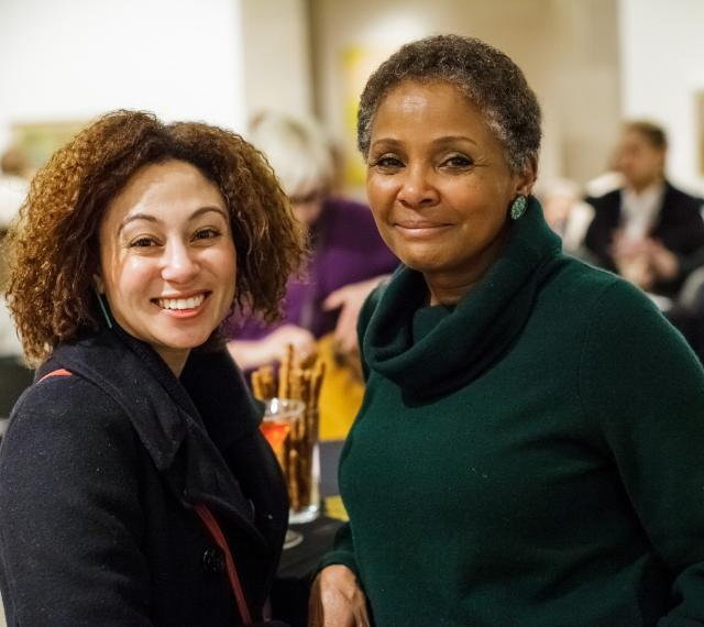 two women leaning on a high top table and smiling during free first thursday