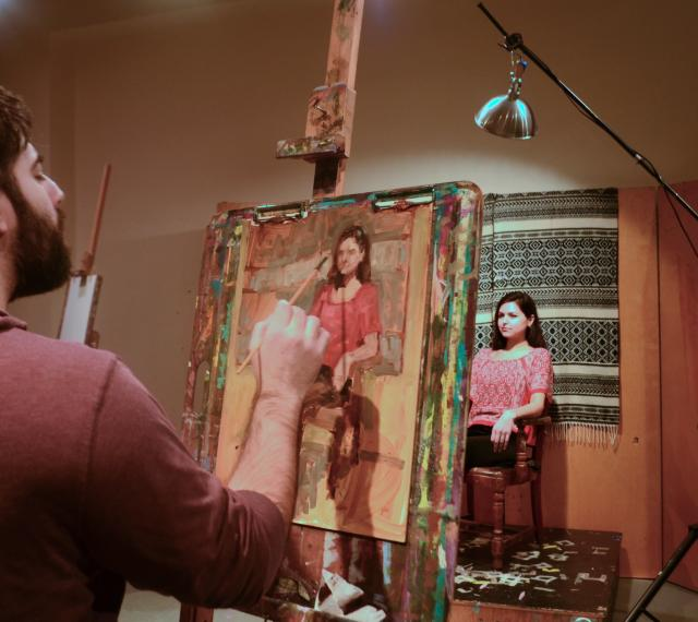 A student is painting a live model in class.