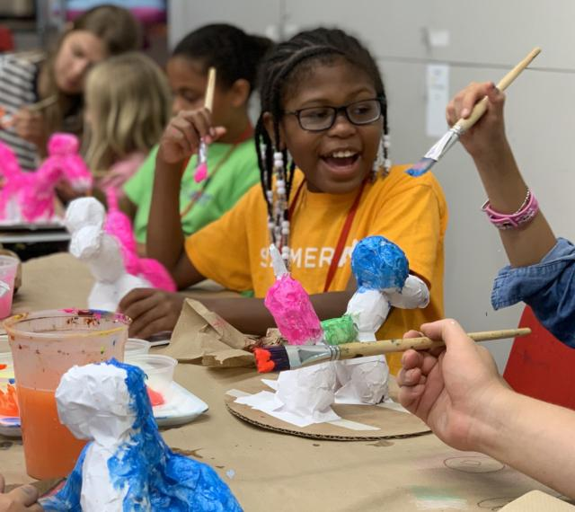 Children are working at a table on colorful papier mache projects in summer camp.