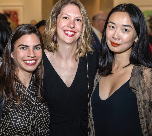 Three visitors are smiling for the camera at an event in the galleries.