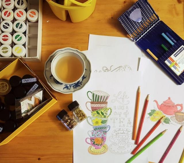 A photo from above of a workspace with colored pencils, paints drawings, and tea.