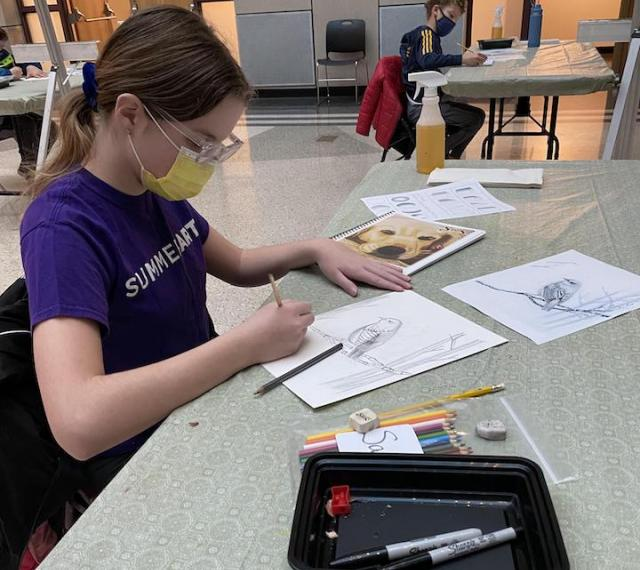 A young art student is drawing a bird in the foreground. Another student is working at a separate table in the background.