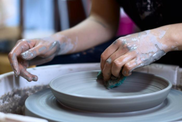 A student is shaping a plate with a sponge on the pottery wheel. Only their hands are visible.