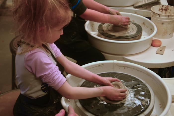 A young student is working on the pottery wheel with both hands. Another yound student is at a wheel next to her, but we can only see their hands.