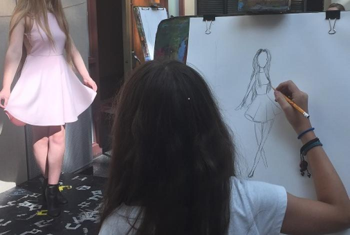 A teen is drawing on an easel. We can see the back of their head and the drawing of a live model posing for fashion illustration.