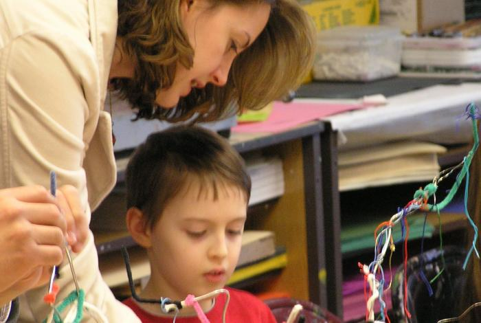 a parent and child are working together on an art project with pipe cleaners.