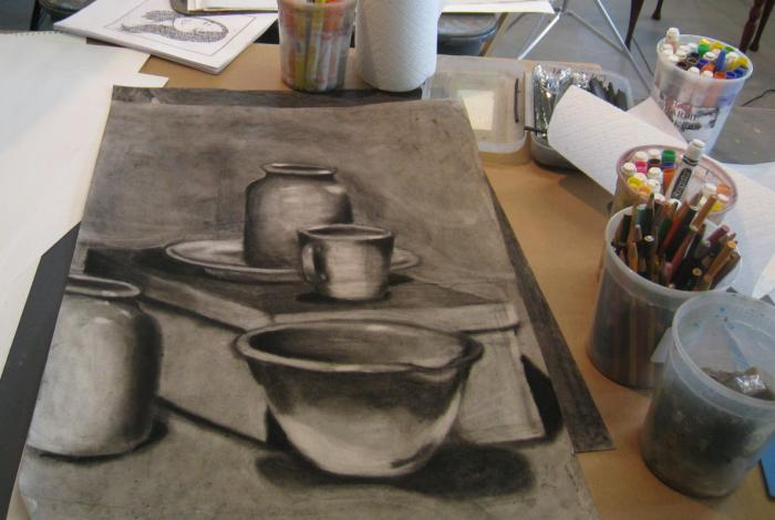 A student's workspace on a table in the studio from the view of the student. A Large sketchbook is in front of us, with a charcoal drawing of some bowls and bottles. To the right is a couple of cups full of pencils and other drawing utensils.