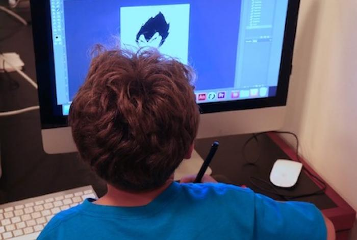A child is sitting at a computer and using a digital tablet and stylus to draw on the screen. The back of their head is facing us.