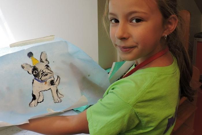 A child is holding up a painting that she made of a dog.